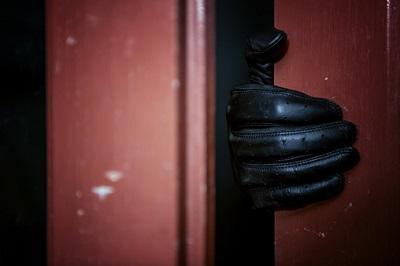 Einbrecher mit Handschuh an der Tür