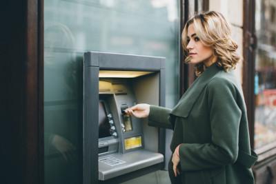 Eine Frau hebt am Geldautomaten Geld ab.