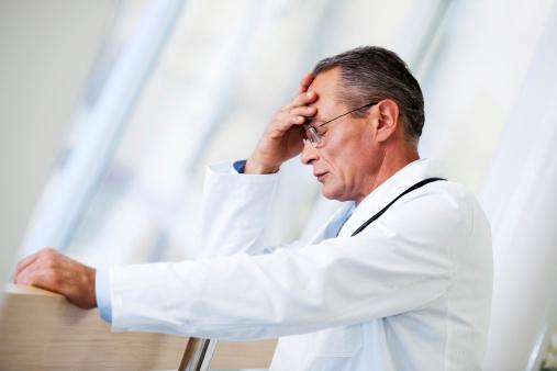 Ein verzweifelter Arzt stüzt mit der Hand seinen Kopf ab.