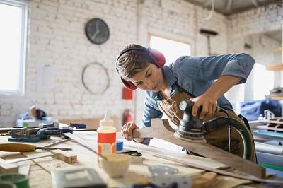 Tischlerin schleift Holz in einer Werkstatt.