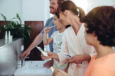 Familie beim Zähneputzen im Badezimmer.