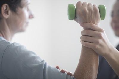 Patient bei einer Physiotherapie mit Hantel in der Hand