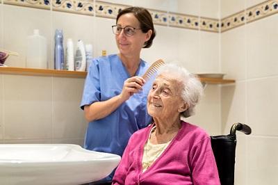 Altenpflegerin kämmt Seniorin im Bad die Haare.