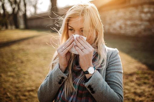 Eine junge Frau im Park hält sich ein Taschentuch vor die Nase.