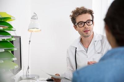 Arzt führt im Sprechzimmer ein Gespräch mit einem Patienten.