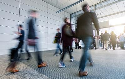 Angestellte gehen im Eingangsbereich eines Büros.
