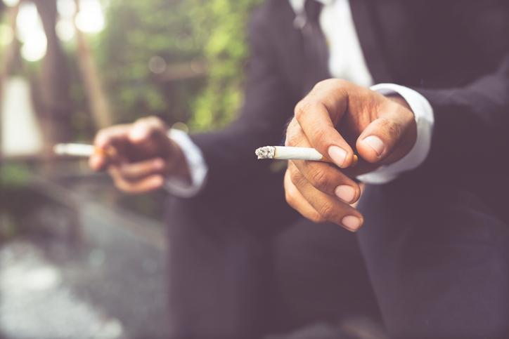 Zwei Männer im Anzug halten Zigaretten in den Händen.