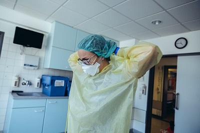 Ärztin zieht Schutzkleidung im Krankenhaus an.