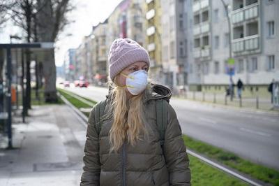 Frau mit Maske an einer Trambahn-Haltestelle in Berlin