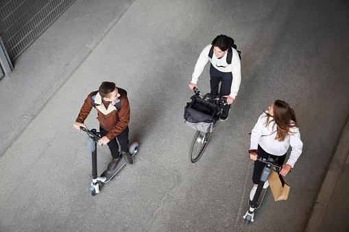 Drei Personen auf E-Scootern und einem Fahrrad aus der Volgelperspektive