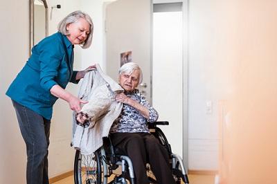 Angehörige hilft Seniorin im Rollstuhl in die Jacke.