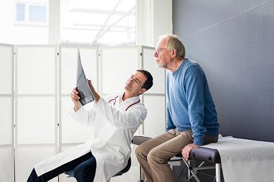 Arzt bespricht mit einem Patienten einen MRT-Aufnahme.