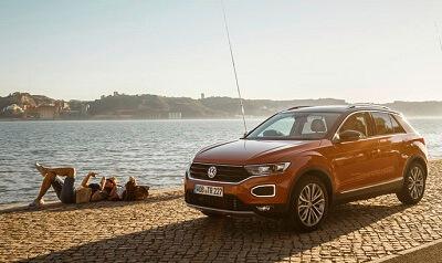 Der rote Neuwagen VW T-Roc an der Uferpromenade eines Sees, Finanzierung mit Online Autokredit und Mehrwertsteuer geschenkt.