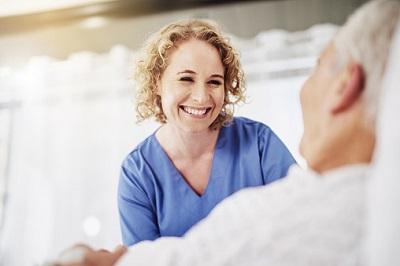 Krankenschwester mit Patient im Krankenhausbett
