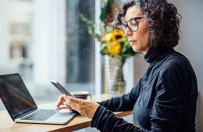 Frau sitzt mit Laptop und Smartphone im einem Café.