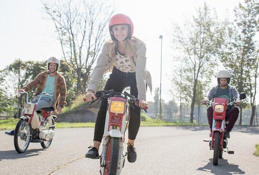 Drei Jugendliche fahren mit ihren Mopeds auf einem Feldweg.