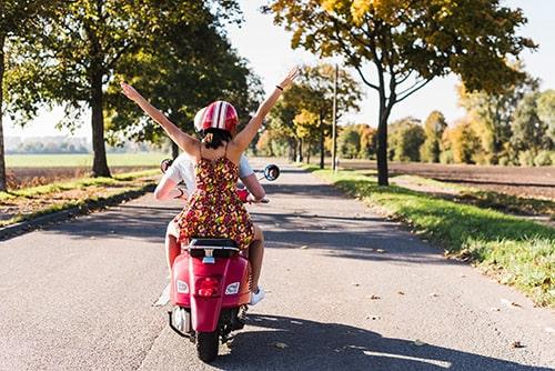 Ein Paar fährt im Sommer auf einem Roller durch die Landschaft.