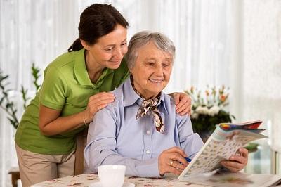 Pflegerin mit älterer Frau in ihrer Wohnung