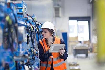 Technikerin mit einem Tablet in einer Produktionshalle.