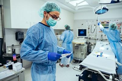 Arzt mit Maske und Pfleger im OP-Saal