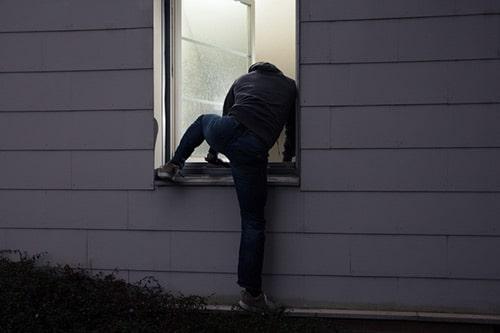 Ein Einbrecher steigt nachts durch das Fenster eines Hauses in eine Wohnung ein.