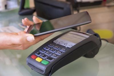 smartphone wird an eine terminal gehalten umd mit apple pay oder google pay zu zahlen