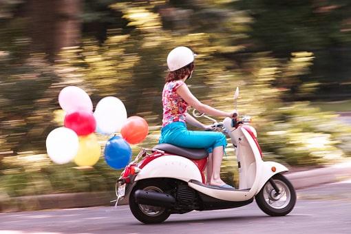 Eine Frau fährt auf einem Roller und zieht dabei Luftballons hinter sich her.