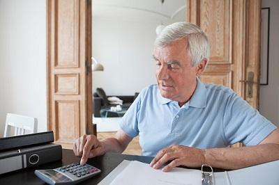 Älterer Mann mit Taschenrechner und Aktenordner in seiner Wohnung
