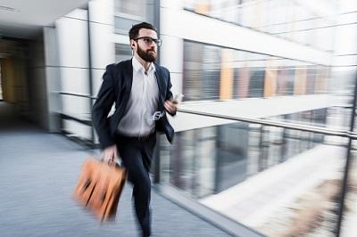 Angestellter eilt durch den Flur eines Bürogebäudes.