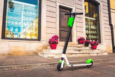 Ein E-Scooter steht in einer Stadt vor einem Schaufenster.