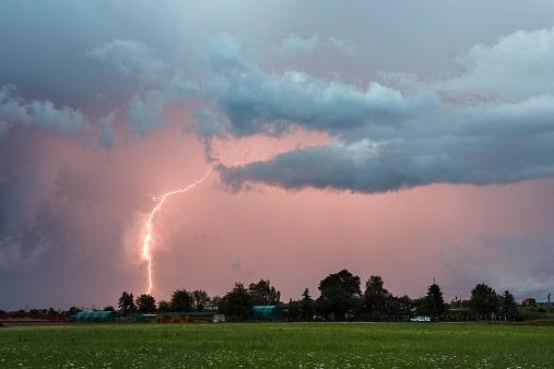 Ein Blitz schlägt über einem Dorf ein, der Himmel ist dabei pink und lila gefärbt.