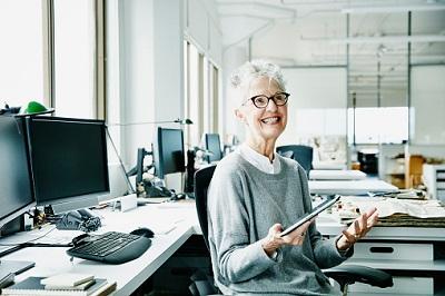 Ältere Angestellte mit Tablet im Großraumbüro