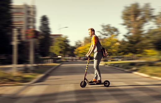 Mann fährt auf einem E-Scooter über eine Straße.