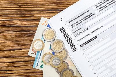 Steuerformular mit Euro-Münzen und Geldscheinen