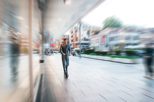 Mann fährt auf einem E-Scooter durch die Stadt.