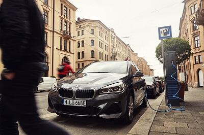 Der Plug-in Hybrid BMW 225xe Active Tourer in dunkler Lackierung an einer Ladesäule in der Münchner Innenstadt, Kfz-Finanzierung über Innovationsprämie und Online-Autokredit.