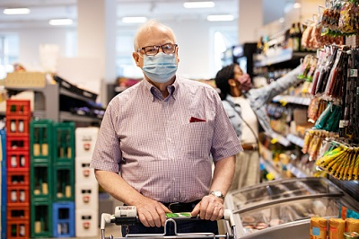 Älterer Mann mit Maske und Einkaufswagen in einem Berliner Supermarkt.