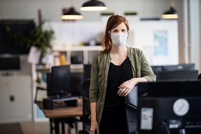 Junge Angestellte steht mit Maske im Großraumbüro