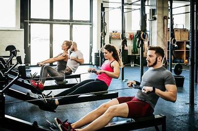 Besucher eines Fitness-Studios an Rudermaschinen.