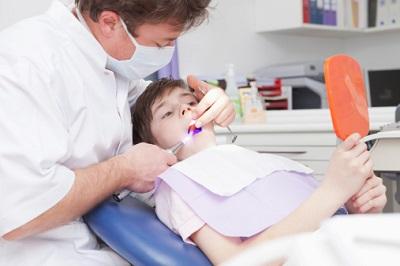 Junge beim Zahnarzt im Behandlungsstuhl