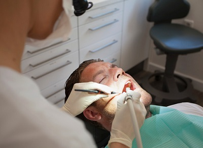 Zahnärztin behandelt Patienten im Behandlungsstuhl.