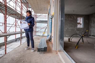 Frau steht auf einer Baustelle