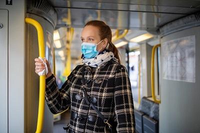 Junge Frau während Covid-19-Ausbruch mit Maske in der U-Bahn