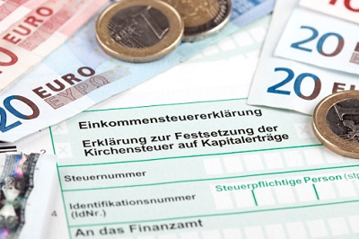 Vordruck Steuererklärung mit Geldscheinen und Münzen