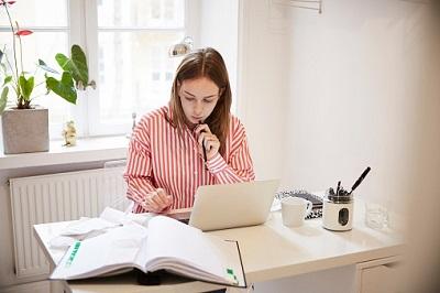 Junge Frau am Laptop mit Papieren.