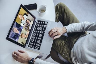 Mann mit Laptop bei einer Videokonferenz im Homeoffice