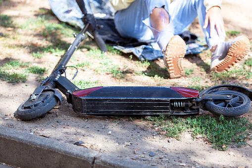 Ein E-Scooter liegt am Boden, im Hintergrund sitzt eine leicht verletzte Person, die man nur halb sieht.