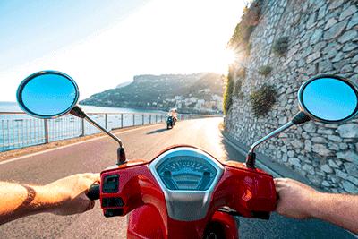 Ein Roller fährt, aus der Fahrerperspektive gesehen, auf einer Küstenstraße im Sommer.