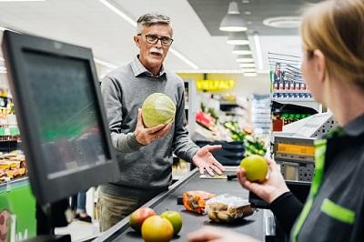 Älterer Mann spricht im Supermarkt mit einer Kassiererin.