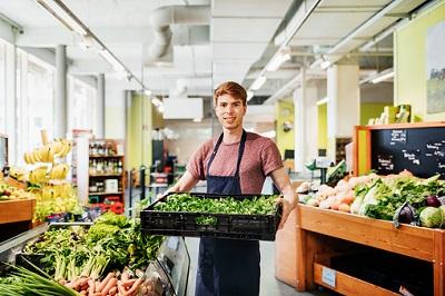 Verkäufer im Supermarkt mit einer Kiste Gemüse
